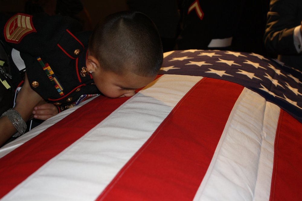 Anthony Ortiz Rivera, 3, kisses his father's casket during preparations for internment at Arlington National Cemetery. Photo courtesy of Veronica Ortiz Rivera.