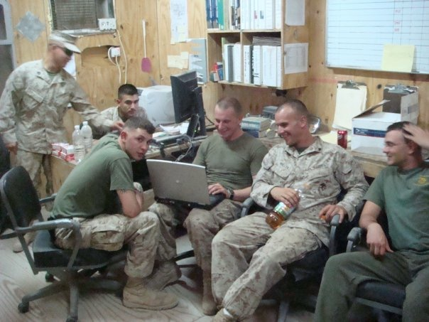 Stewart and Mallek sit next to the man holding computer. Photography taken in weld shop office in Fallujah. Courtesy: Ryan Mallek