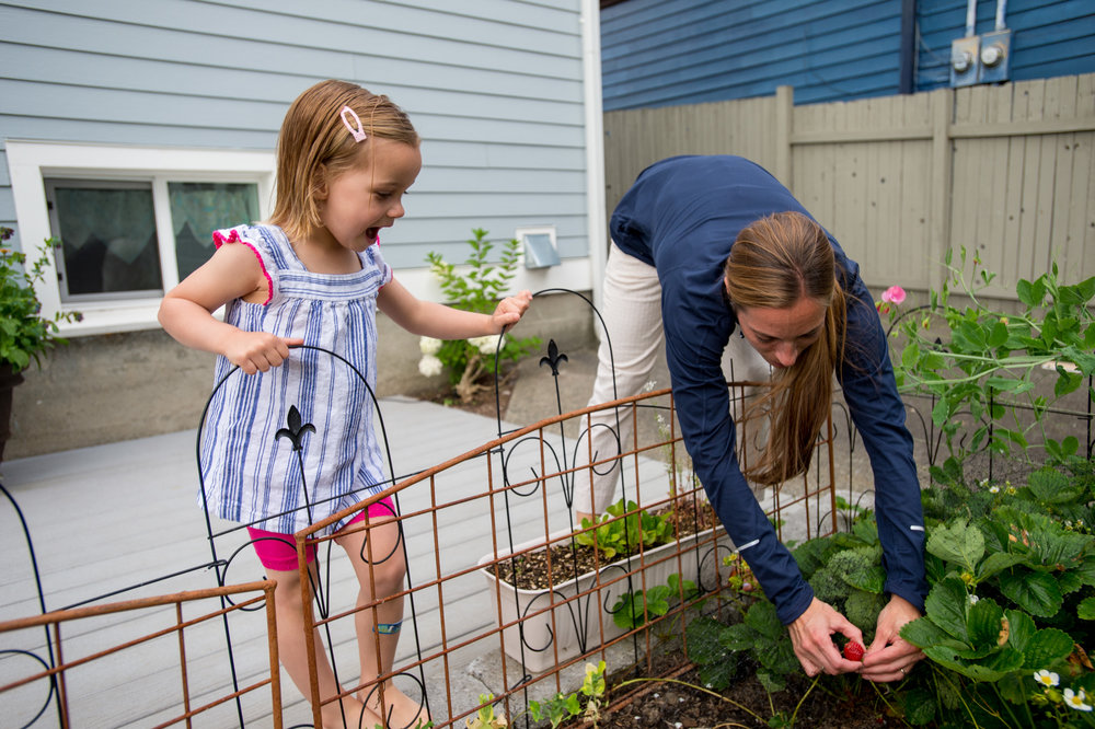 Sarah Roberts at her home in Seattle, Wash., picking home grown strawberries with her daughter Katelyn, 3 after returning from work with Team RWB. Photo by Stuart Isett for The War Horse