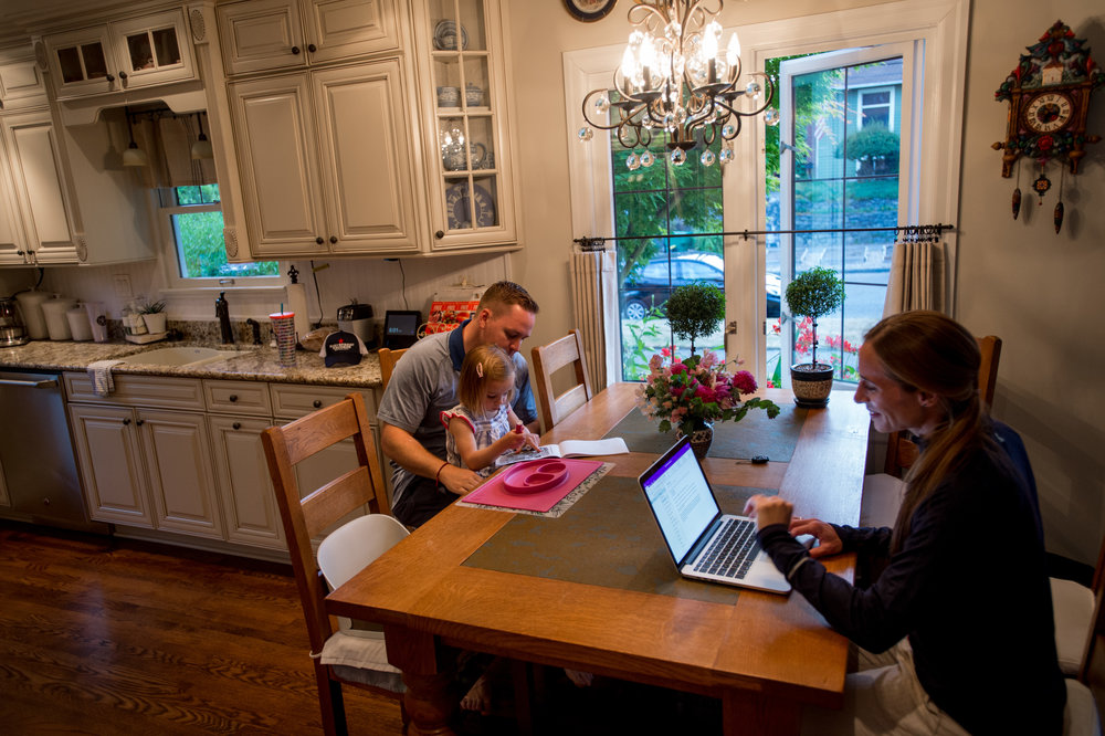 Sarah Roberts at her home in Seattle, Wash., with her daughter Katelyn, 3 and husband Jeff, 36. Roberts is checking her email after returning home from work. Photo by Stuart Isett for The War Horse
