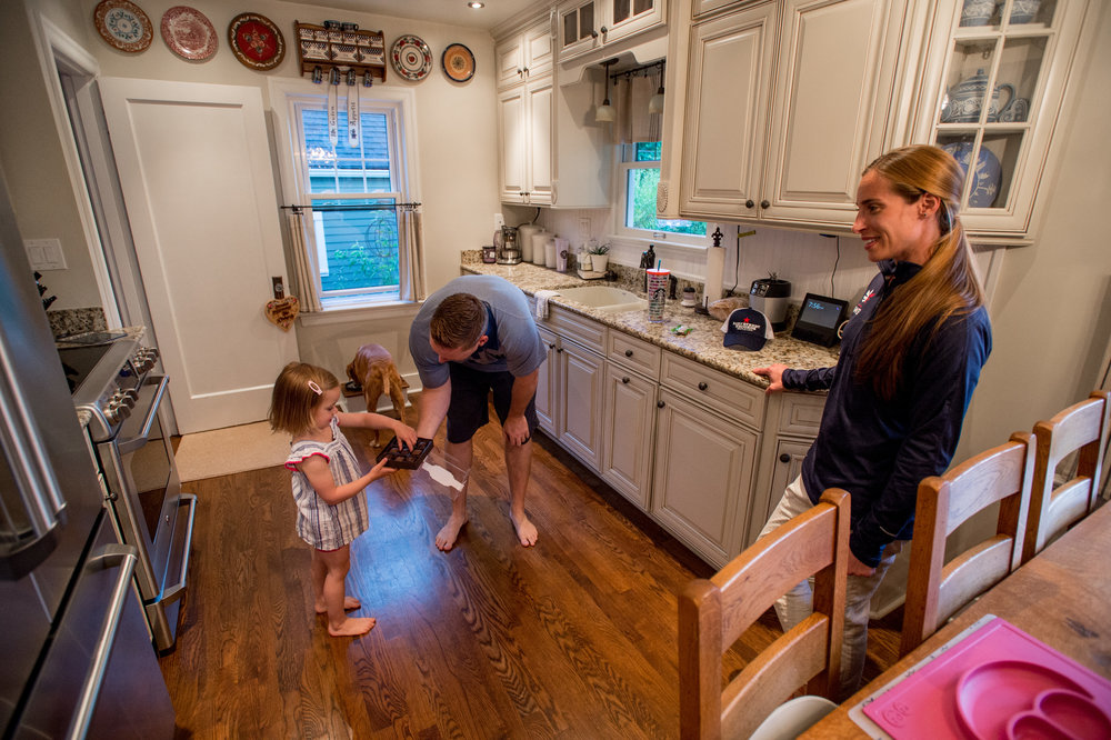 Sarah Roberts at her home in Seattle, Wash., with her daughter Katelyn, 3 and husband Jeff, 36. Here Jeff is sharing a chocolate with their daughter. Photo by Stuart Isett for The War Horse