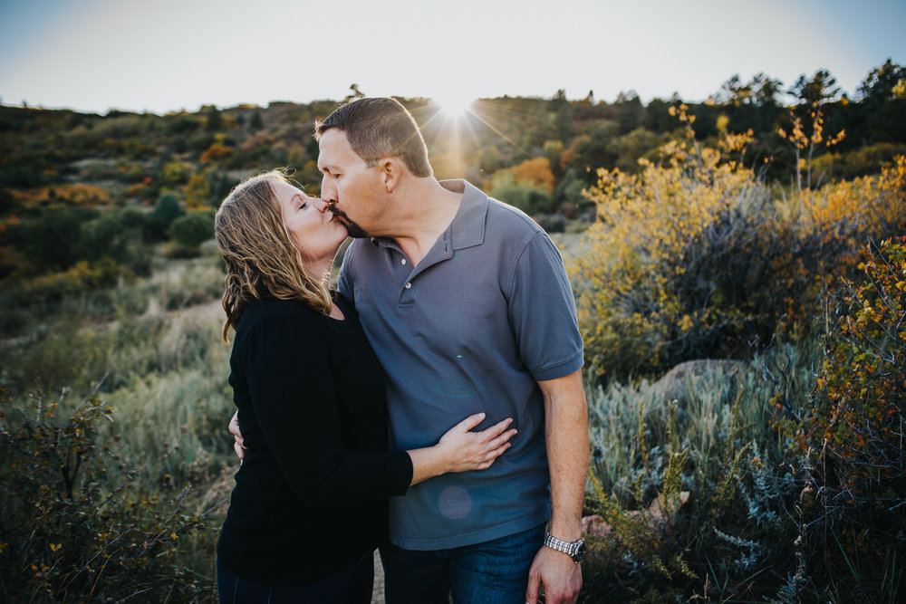 Couple kissing during family session at mountain view open space in Colorado Springs.