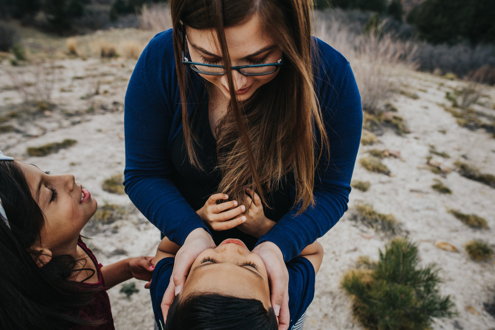 Single mother loves on her children during their family session in Colorado Springs.
