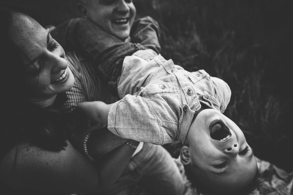Mother and father snuggle with their laughing son during their session at Cheyenne Mountain State Park in Colorado Springs.