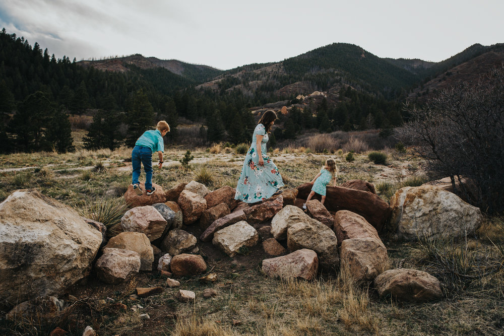 Family of three adventures on rocks in Colorado Springs mountain family session.