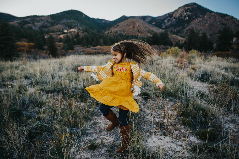 Little girl dancing in the mountains during family photo session in Colorado Springs.