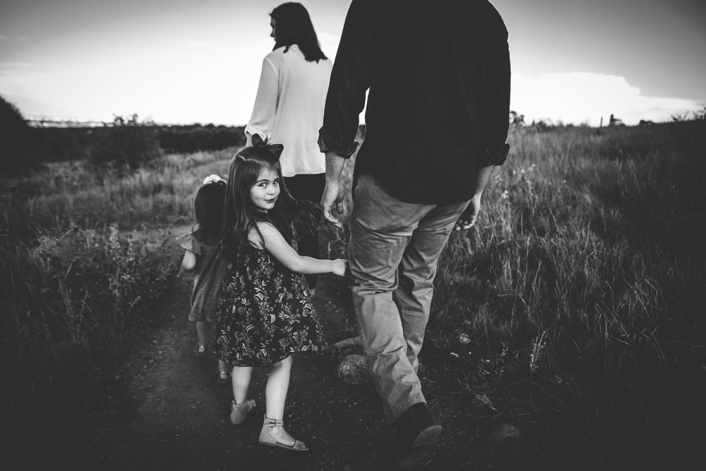 Military family of four hikes in Colorado Springs open space during family photography session.