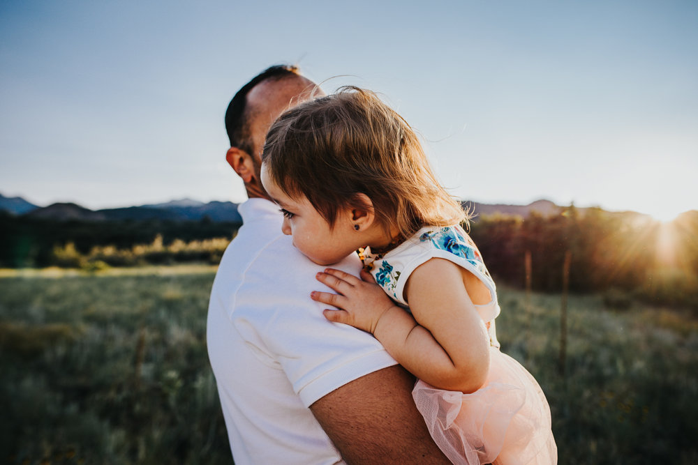 Military dad and his daughter share an embrace during family photo shoot in Colorado Springs open space.