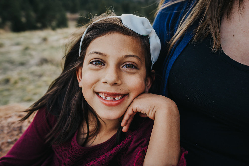 Little girl snuggles with her mother and smiles during family session in Colorado Springs open space.