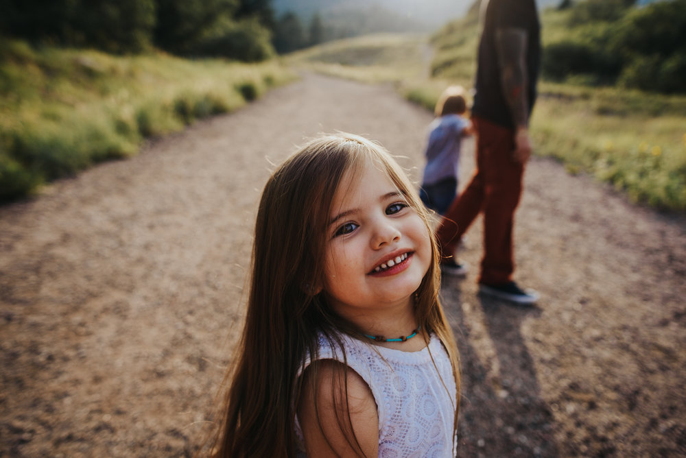 Sweet girl smiles and plays with her family during a family photo session in Colorado Springs.