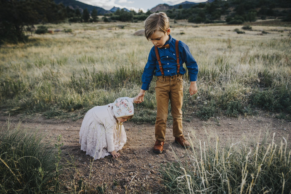 Brother helps little sister on a hike during Colorado Springs family photo session.