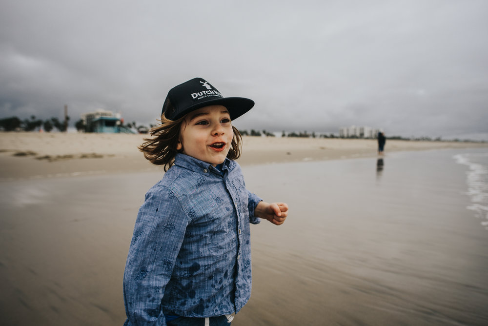 Little boy enjoying a run along the coast in California.