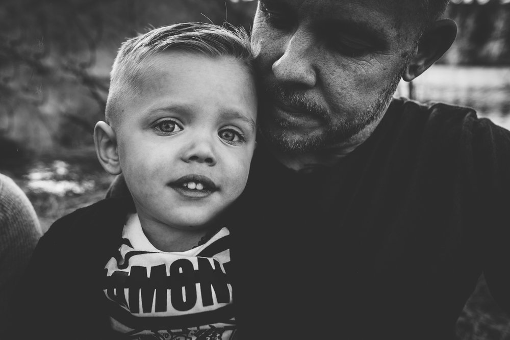 Father and son snuggle during family photography session at Red Rock Open Space in Colorado Springs