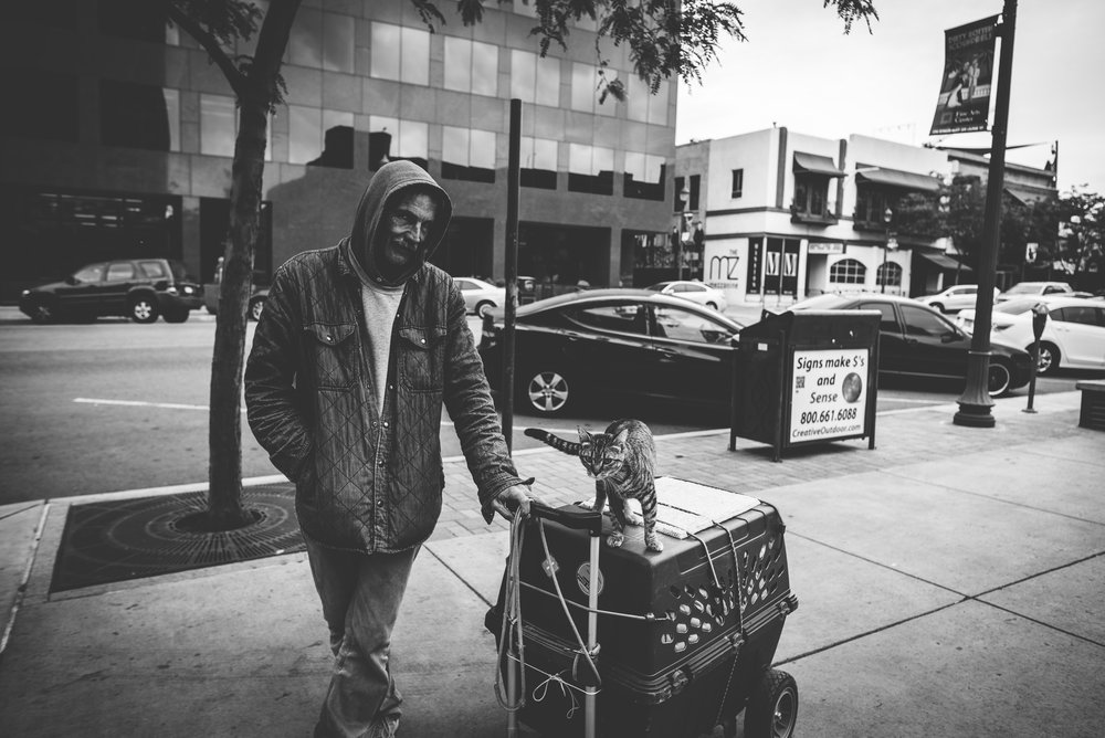 Homeless man takes his cat for a stroll in downtown Colorado Springs.