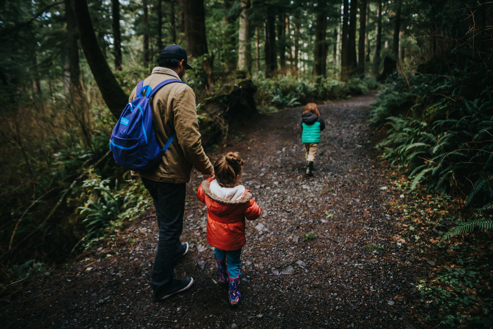 A dad walks with his two small children on path in Oregon forest.