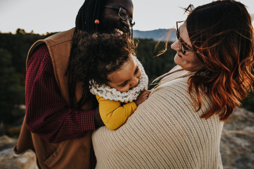 Family snuggles with their daughter during a family session at Palmer Park in Colorado Springs.
