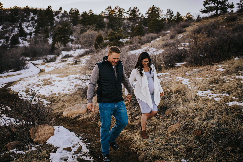 Couple walks on trail in Colorado Springs mountains during maternity session.