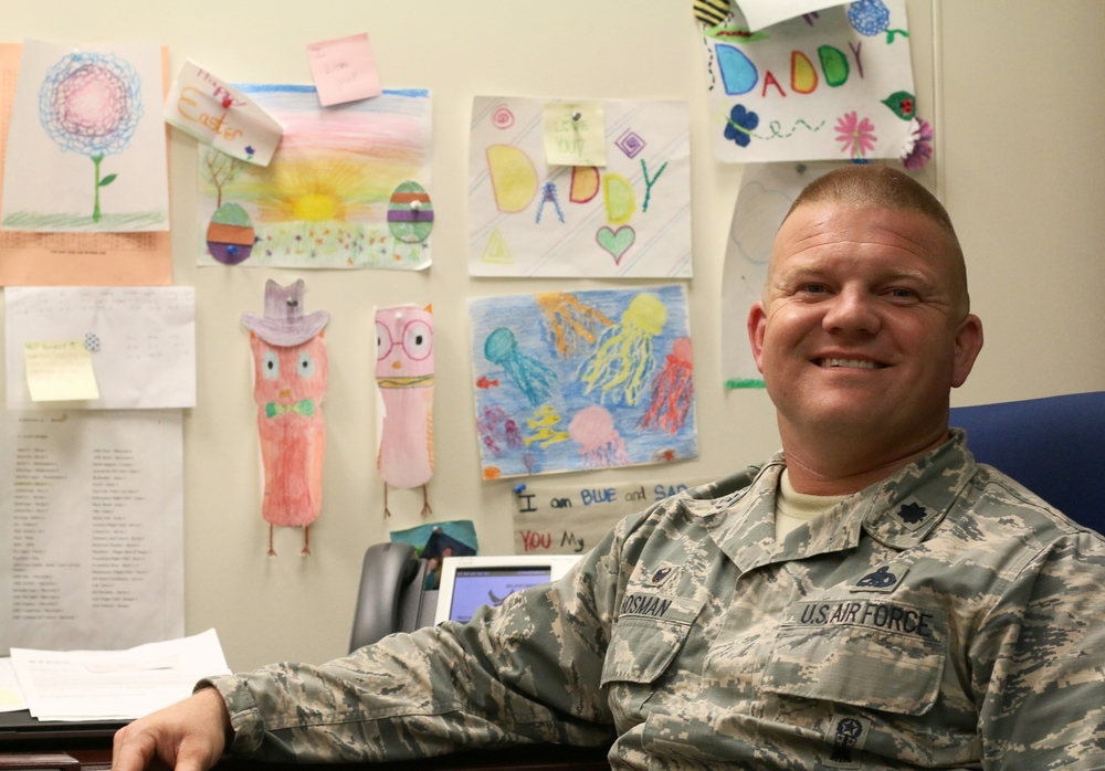 Lt. Col Hosman sits at his desk in front of hand-drawn pictures from his daughter.