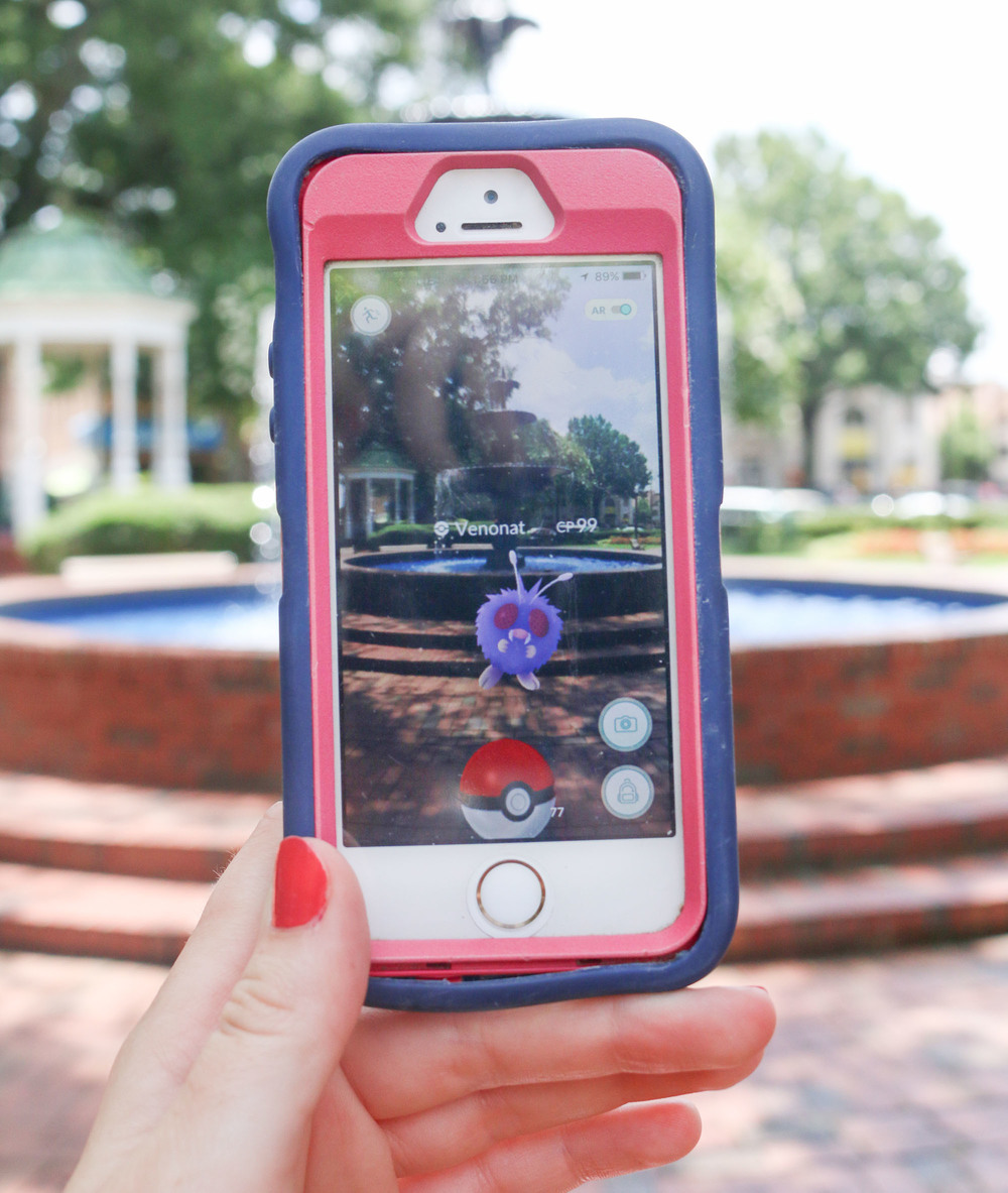A photo of the popular Pokemon Go app shows a Venonat Pokemon in front of the fountain in the Marietta Square on Tuesday. The app uses augmented reality to combine the real and virtual world to allow players to catch Pokemon in their own envrionments. Staff- Emily Selby