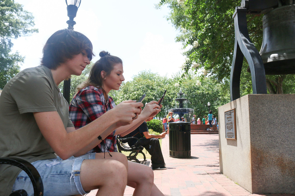 Stephen Sprinkle (front), 18, of Marietta, plays Pokemon Go with Haley Elder, 21, of Marietta in the Marietta Square on Tuesday. Staff- Emily Selby