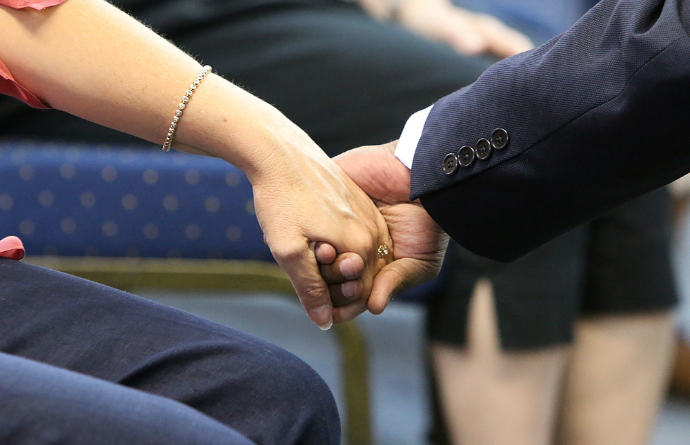 Attendees at a prayer vigil hold hands during a prayer at the House of Hope International Empowerment Center in Marietta on Wednesday. Staff- Emily Selby