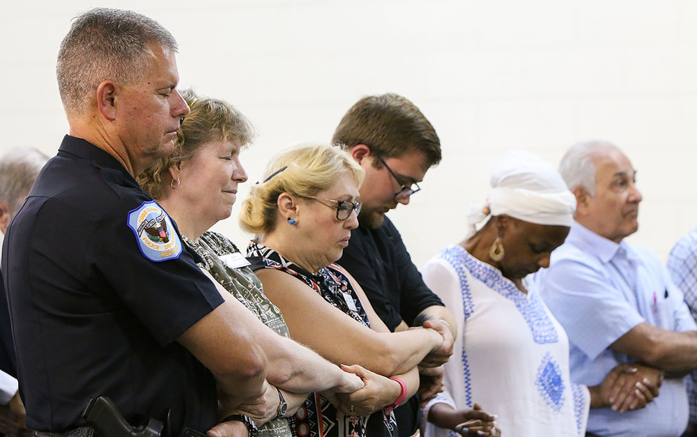 Marietta Dep. Chief Tim Cox joins hands in prayers at a prayer vigil at the House of Hope International Empowerment Center in Marietta on Wednesday. The vigil, hosted by the Cobb chapter of the Southern Christian Leadership Conference, promoted untiy and community. Staff- Emily Selby