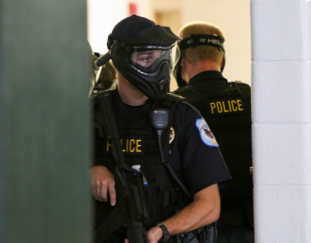 A Cobb Police officer watches from a doorway as her team works through the active shooter training event on the Marietta Kennesaw State University campus on Monday. The officers will complete three simulations that increase in difficulty throughout the day. Staff - Emily Selby