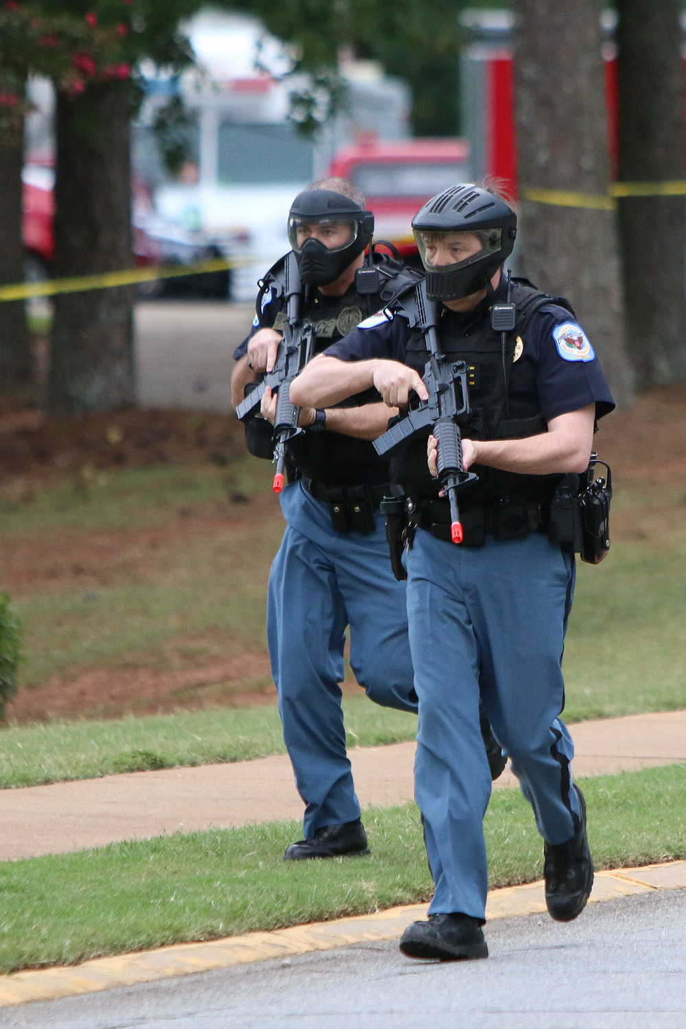 Two officers run as they arrive on the scene of simulated active shooter event for training at the Marietta KSU Campus on Monday. The annual training involves all officers in Cobb. Staff - Emily Selby