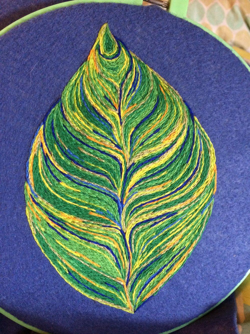 An embroidered leaf on felt.