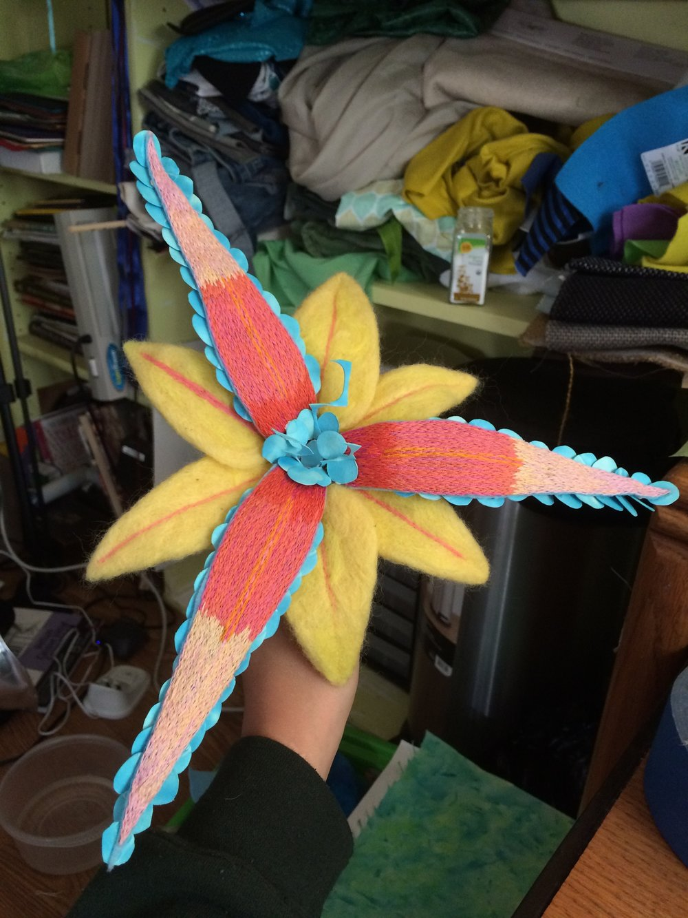 A flower made from wool felting, embroidery, watercolor paintings, and wire.