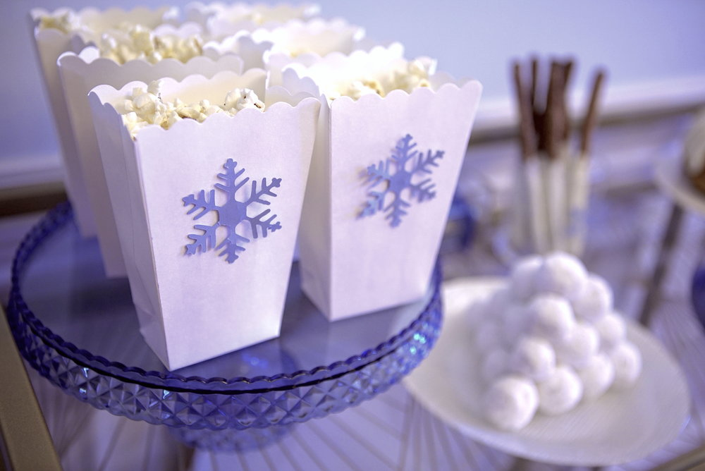 I cut out snowflakes with my Cricut machine to jazz up these popcorn bags from Michael's. The cake stand is from Homegood's!