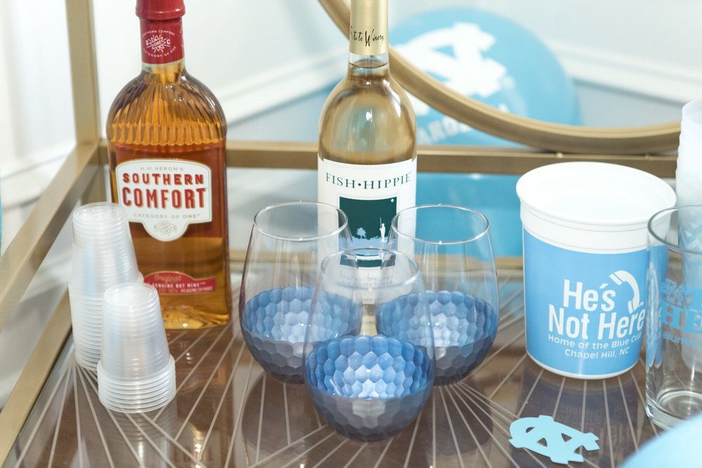Southern Comfort and NC's Fish Hippie Wine for those that don't love beer.And of course, no UNC game day is complete without a blue cup from He's Not Here!