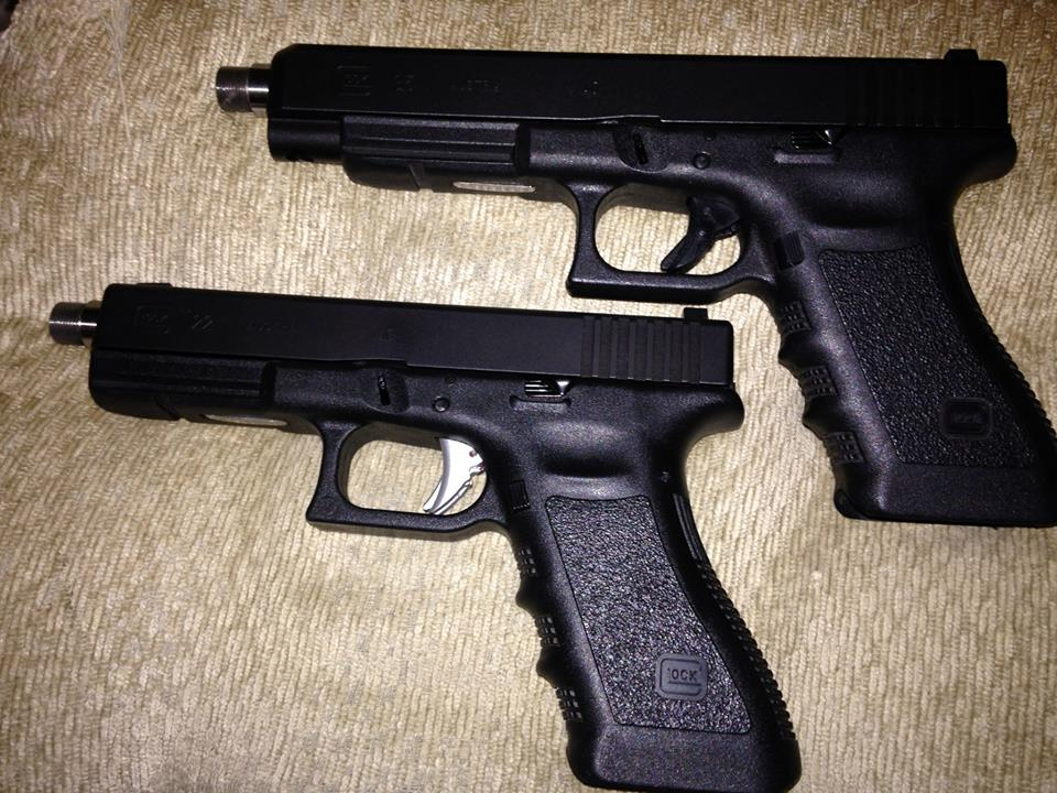 Glock 22 w/ UAT on bottom, Glock 35 on top with stock factory unit.