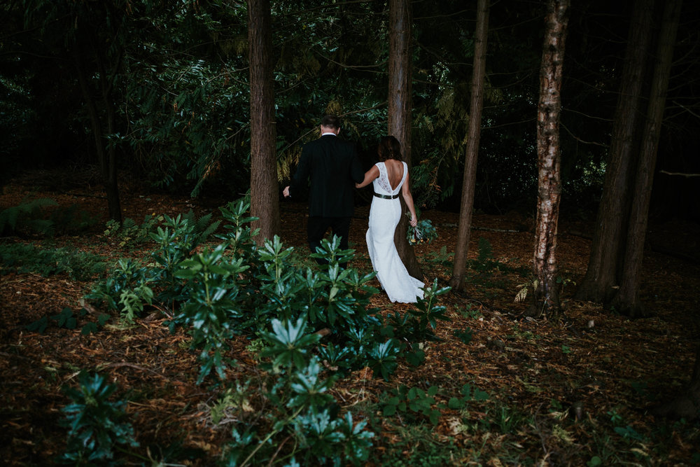 Bride and groom are walking together in the forest.