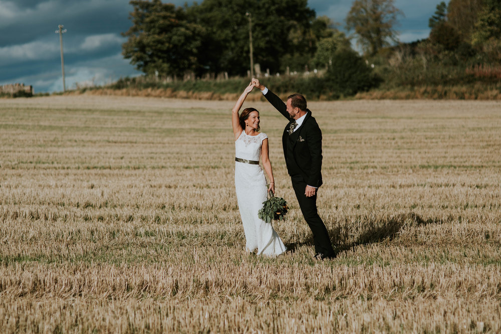Bride and groom are dancing on the fields.