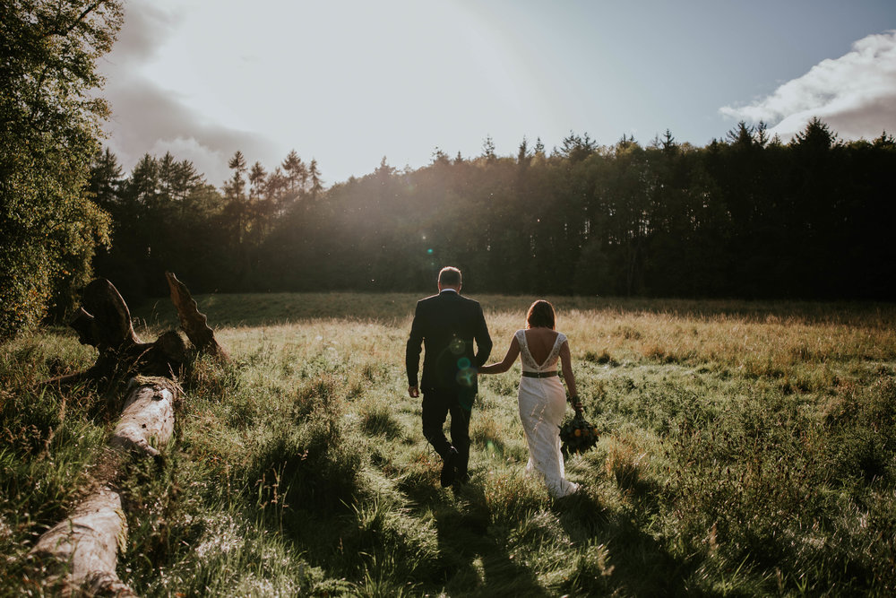 Bride and groom are walking together on the fields.