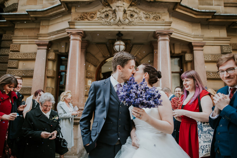 Bride and groom are kissing after the gorgeous confetti shot in Glasgow