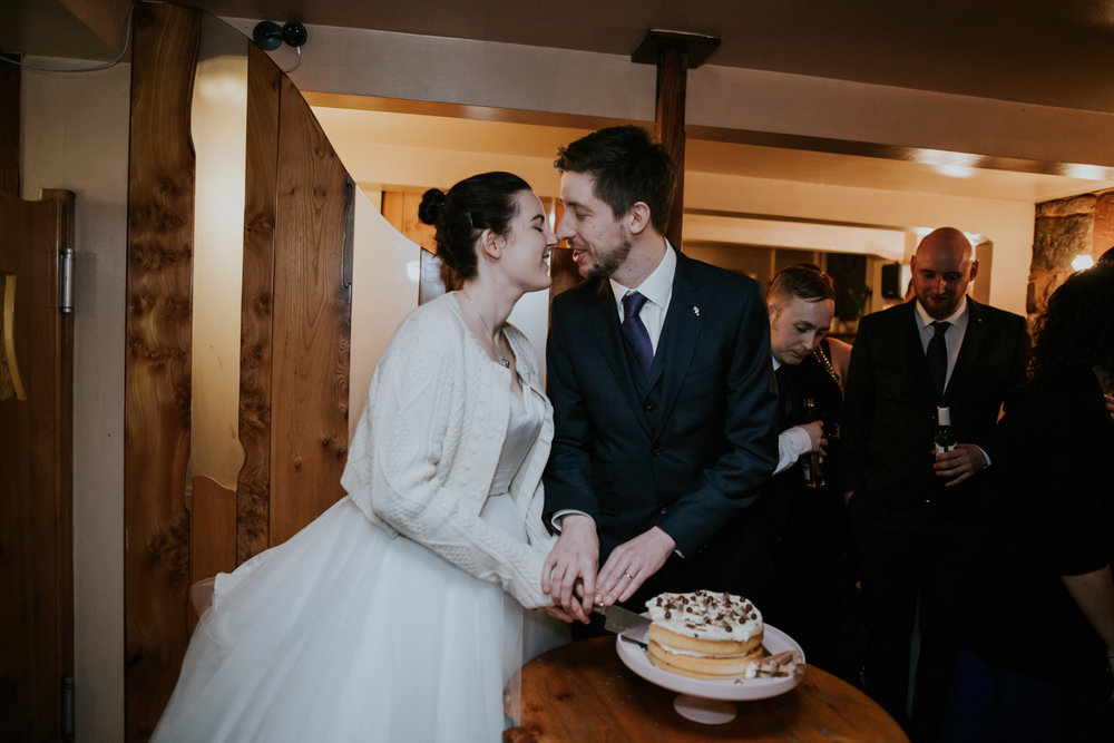 Bride and groom are cutting the cake in the Brooklyn cafe in Shawlands, Glasgow