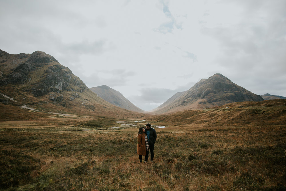 Couple is standing in a natural mountain environment in Glencoe, Scotland
