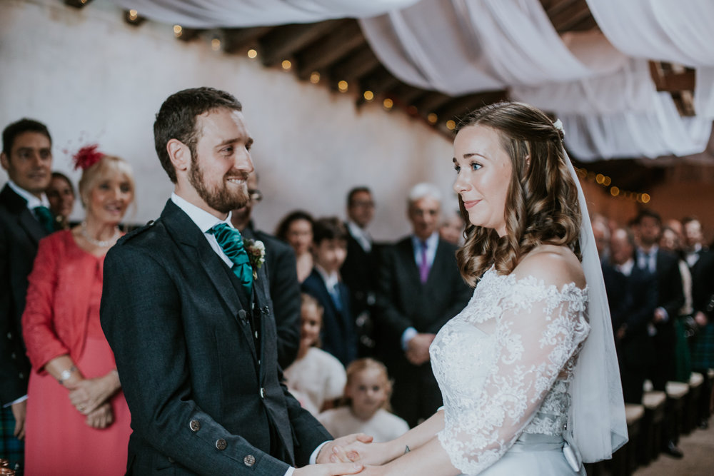 Groom holds brides hands and looking at her with a love