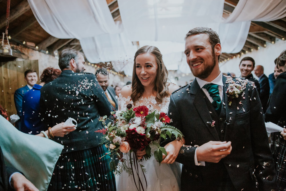 Bride is holding the stunning Briar Rose Design bouquet during the confetti shot at Harelaw farm wedding