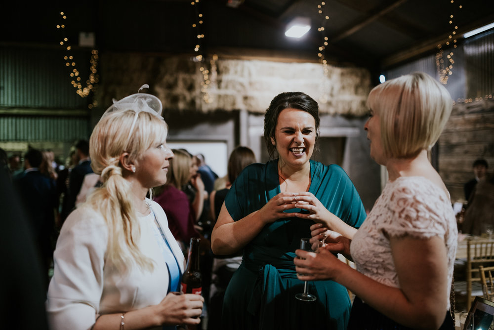 One of bridesmaid is laughing with other guests at the Harelaw farm wedding reception