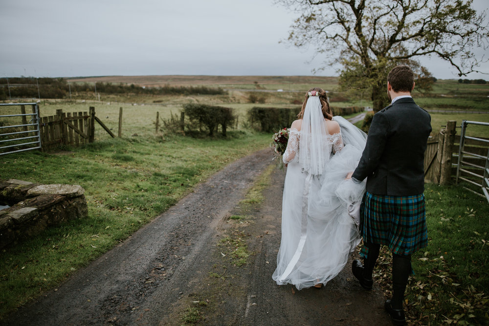 Groom is helping his boho bride to carry on her Flossy and Dossy wedding dress. Harelaw barn, Ayrshire