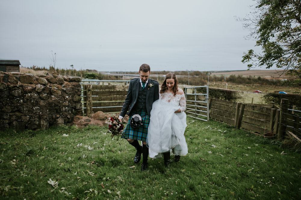 Bride and groom are walking together. Groom is holding Briar Rose Design wedding bouquet. Harelaw farm wedding venue.