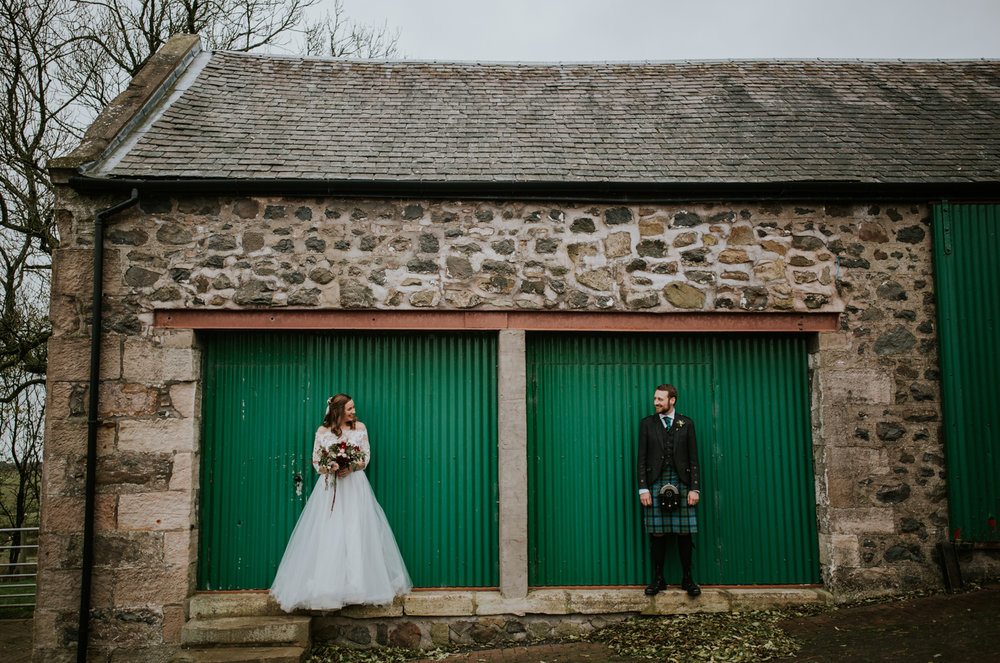 Bride and groom are standing next to the green doors at Harelaw farm wedding venue.