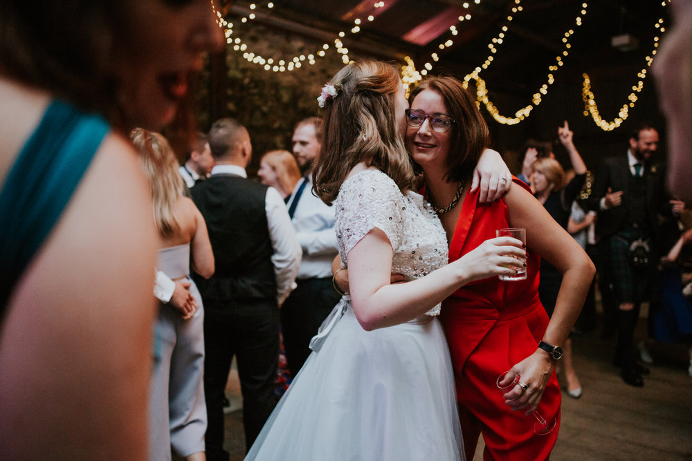 Bride is cuddling the wedding guest at the dance floor at Harelaw farm DIY wedding in Ayrshire.