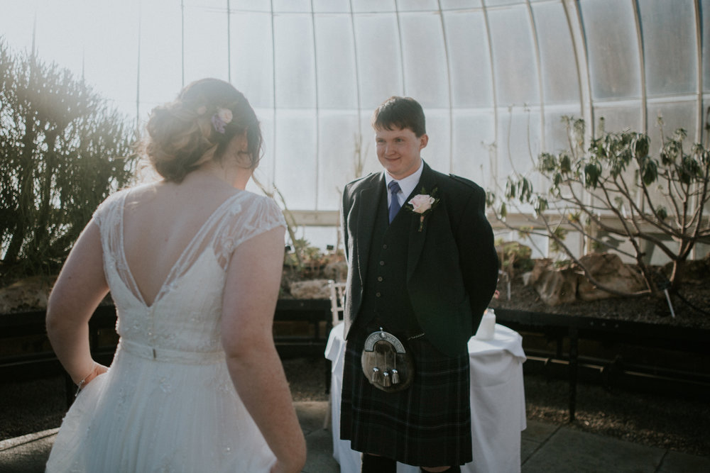 The groom looks at the bride with the happy smile on his face