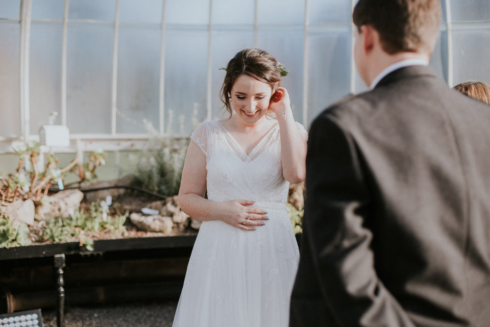 The bride is shiny smiling at the Botanic Gardens in Glasgow