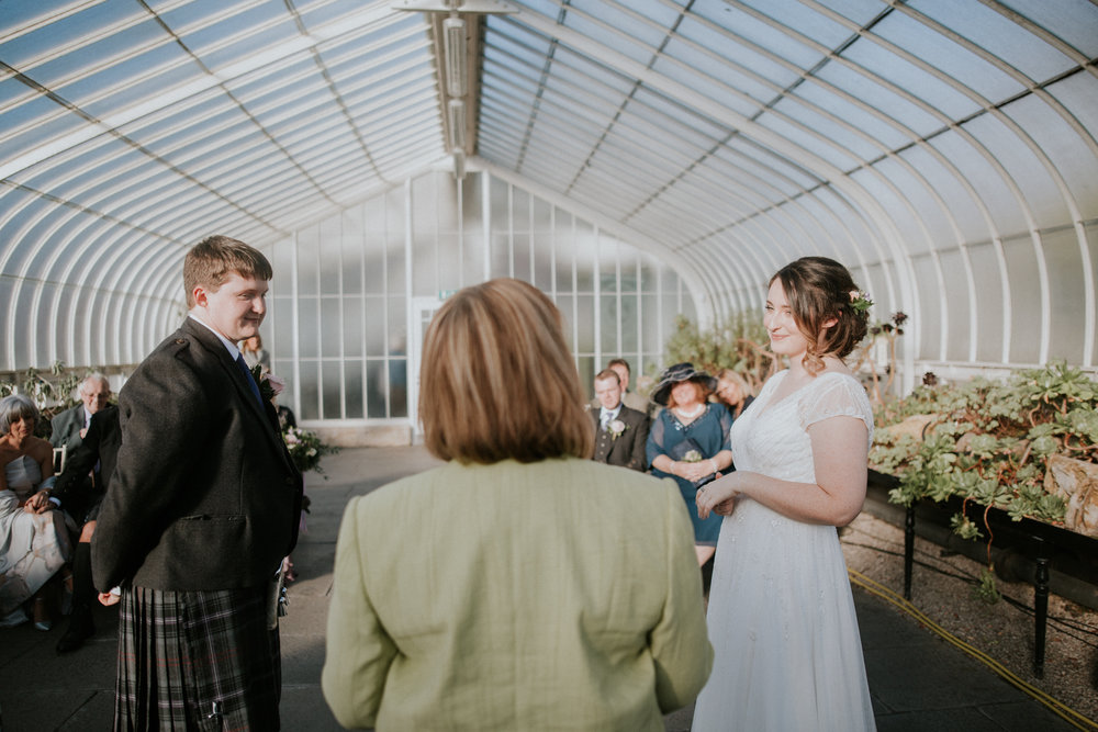Bride and groom at the ceremony in Glasgow Botanic Gardens looking at the celebrant