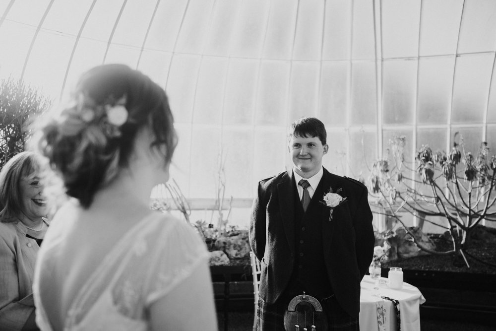 The groom looks at the bride with the big and happy smile